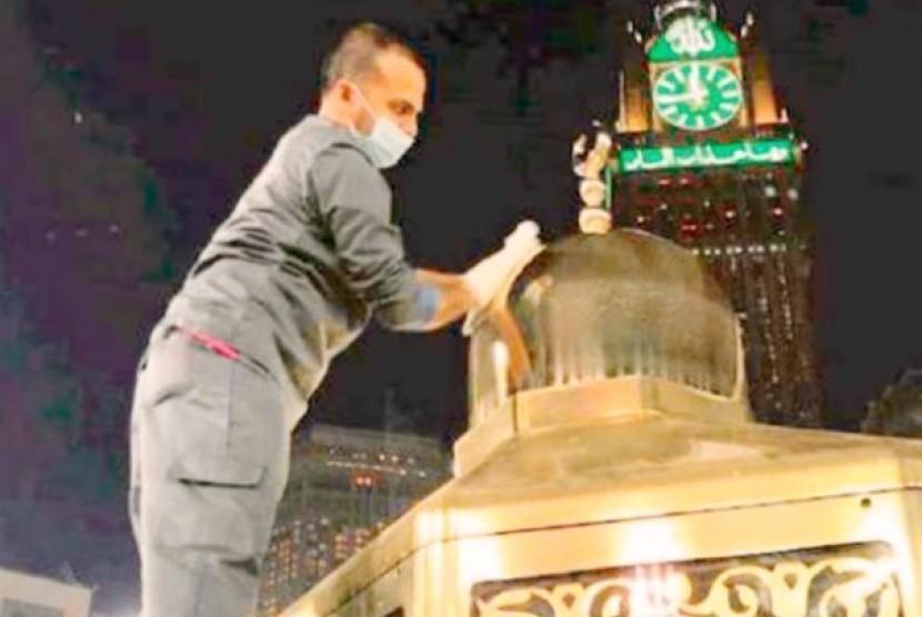 Seorang petugas kebersihan Masjidil Haram tengah membersihkan Maqam Ibrahim.