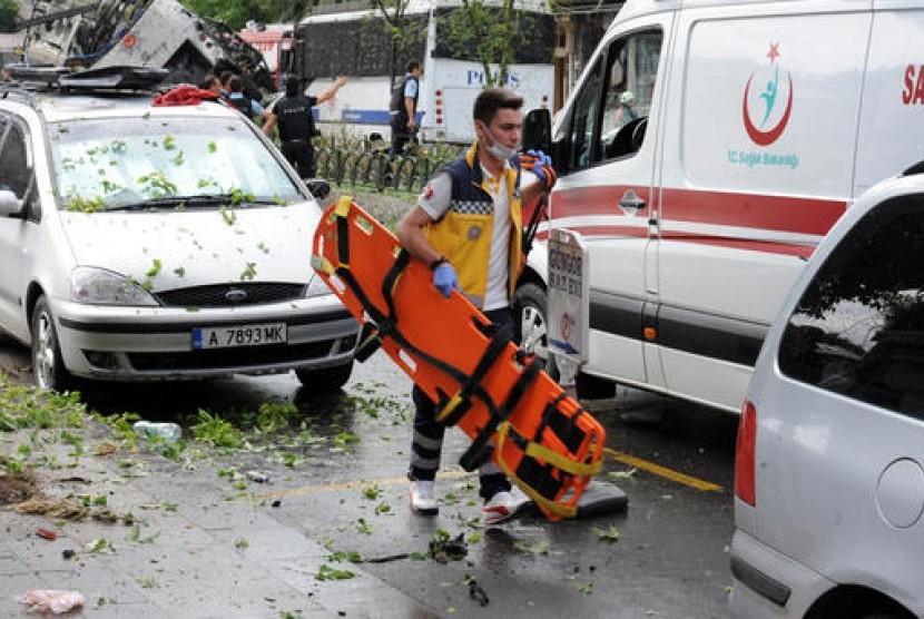 Seorang petugas medis Turki bekerja di lokasi ledakan setelah bus yang membawa polisi antihuru-hara diserang bom di IStanbul, Selasa, 7 Juni 2016.