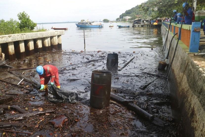 Seorang petugas melakukan pembersihan di lokasi dekat tumpahan minyak di Teluk Balikpapan, Kalimantan Timur, Rabu (4/4).
