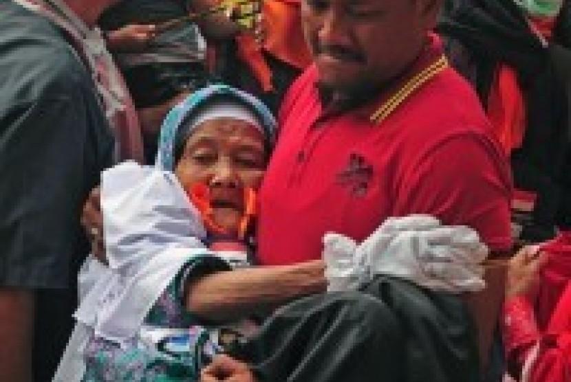 Seorang petugas menggendong seorang calon jamaah haji manula asal Provinsi Riau di Kota Pekanbaru, Rabu (2/9).