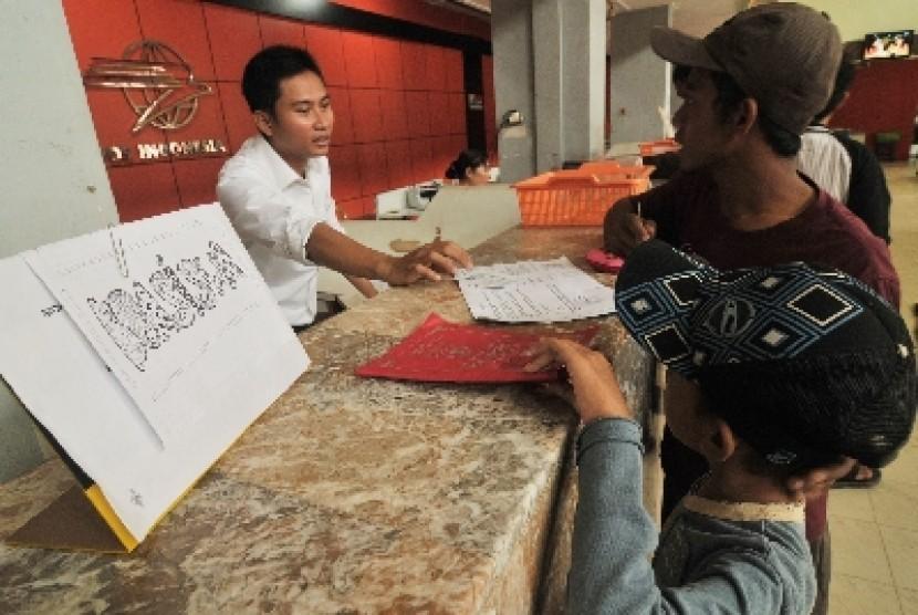 Seorang petugas pos menunjukkan cara pengisian formulir kepada seorang siswa SD untuk pencairan dana Beasiswa Miskin (Ilustrasi)