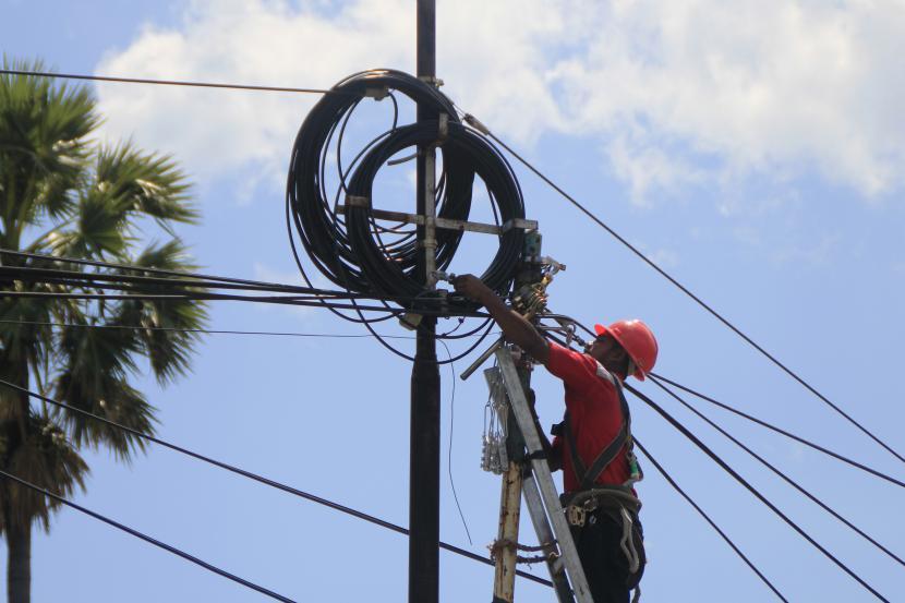 Seorang petugas PT Telkom memperbaiki kabel yang putus. (ilustrasi)