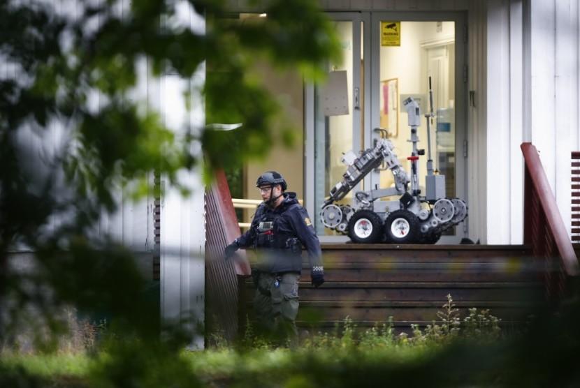 Seorang polisi dan sebuah robot berada di depan Masjid Islamic Center al-Noor di distrik Baerum, Norwegia pascaaksi penembakan pada Sabtu (10/8).