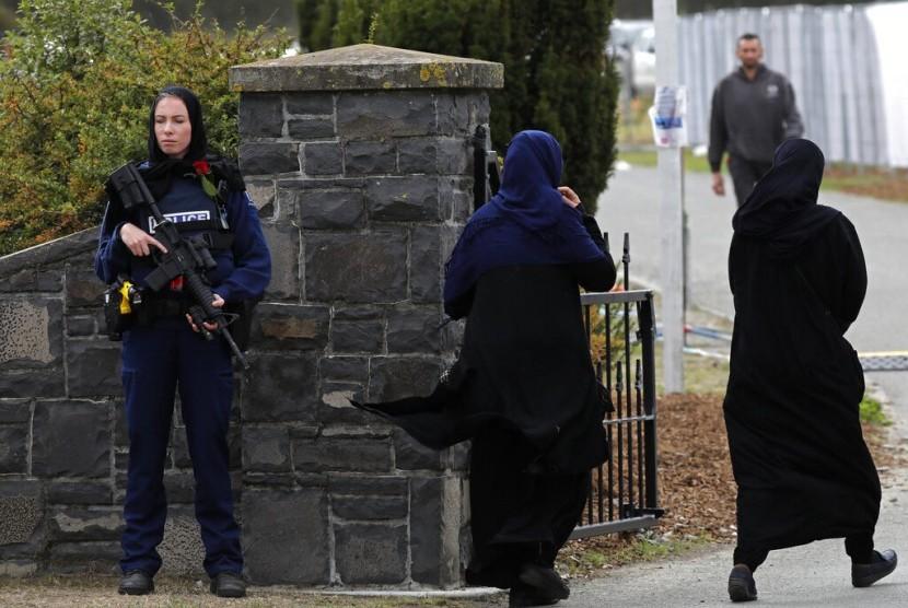 Seorang polisi perempuan dengan bunga mawar berjaga di pemakaman korban penembakan di Memorial Park Cemetery, Christchurch, Selandia Baru, Kamis (21/3).