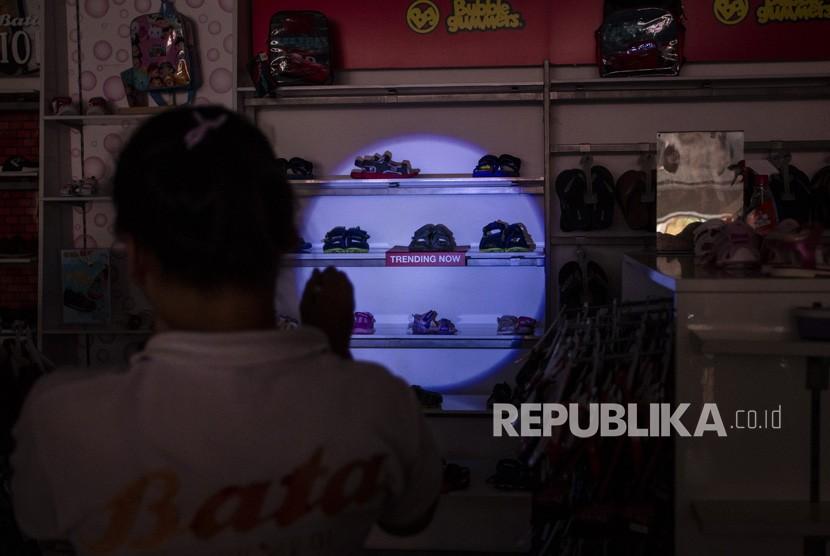[ilustrasi] Seorang pramuniaga merapikan susunan sepatu di Pasar Baru yang mengalami pemadaman listrik, Jakarta, Senin (5/8/2019).