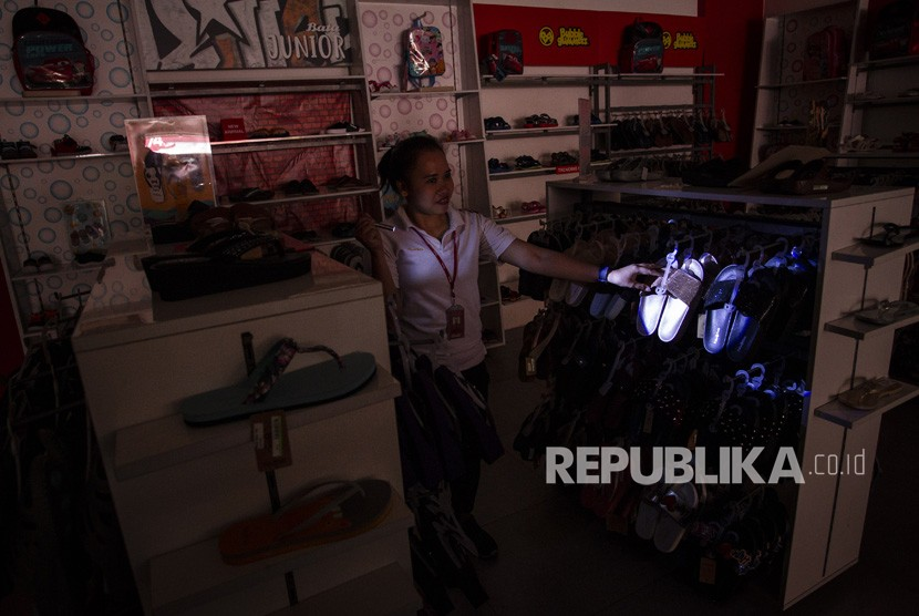 Seorang pramuniaga merapihkan susunan sepatu di kawasan Pasar Baru yang mengalami pemadaman listrik, Jakarta, Senin (5/8/2019).