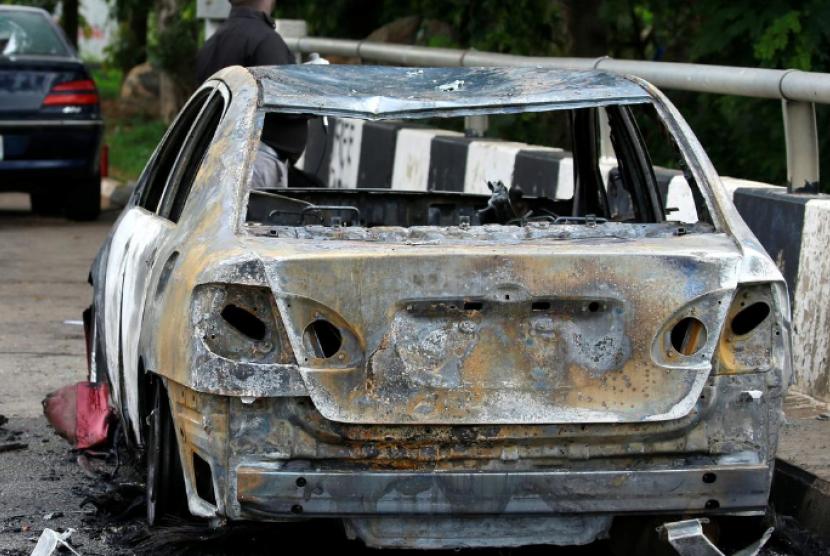 Seorang pria berdiri di dekat bangkai mobil yang terbakar di dekat gedung Parlemen Nigeria usai terjadinya bentrok antara aparat kepolisian dan kelompok demonstran di Abuja, Nigeria, 9 Juli 2019