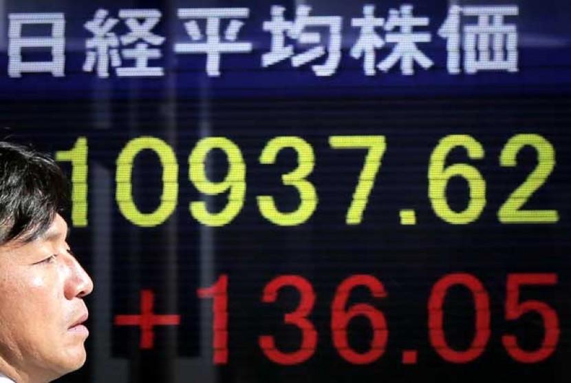 Seorang pria berdiri di depan papan elektronik Nikkei 225 index di Tokyo.