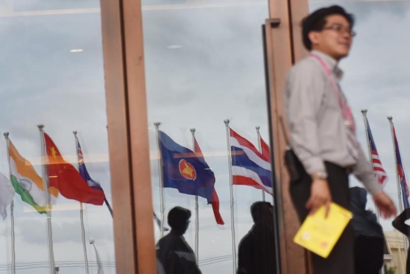 Seorang pria berjalan di depan kaca yang merefleksikan deretan bendera negara peserta Asean Summit ke-28 dan 29 serta Related Summit di National Convention Center, Vientiane, Laos, Minggu (4/9).