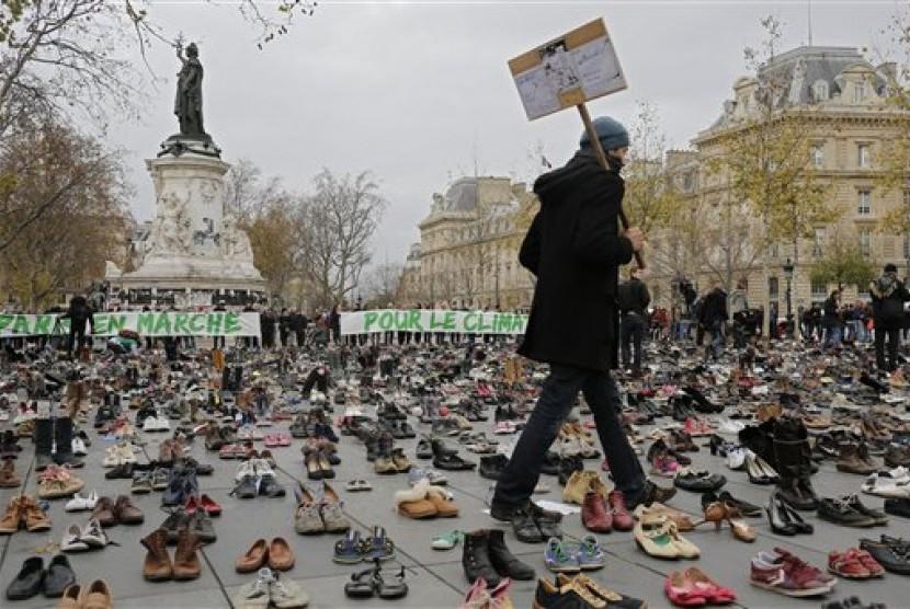 Seorang pria berjalan di tengah ribuan pasang sepatu sebagai bentuk protes perubahan iklim di Paris, Prancis, Ahad, 29 November 2015.