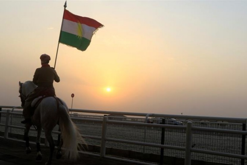 [ilustrasi] Seorang pria Kurdi menaiki kuda dan membawa bendera mendukung referendum di Erbil, Irak.