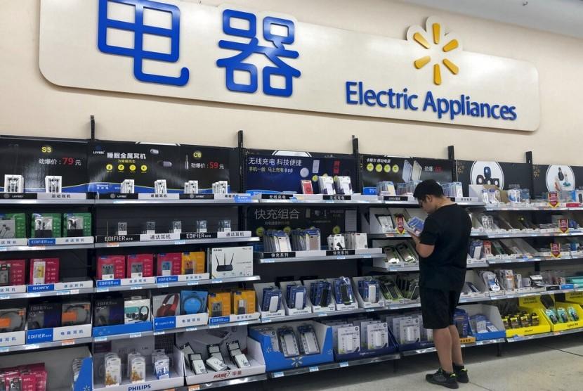 Seorang pria melihat-lihat spesifikasi power bank di sebuah supermarket di Beijing, Kamis (9/5). Ketegangan antara AS dan Cina telah mendorong Presiden Donald Trump meningkatkan tarif impor barang Cina.