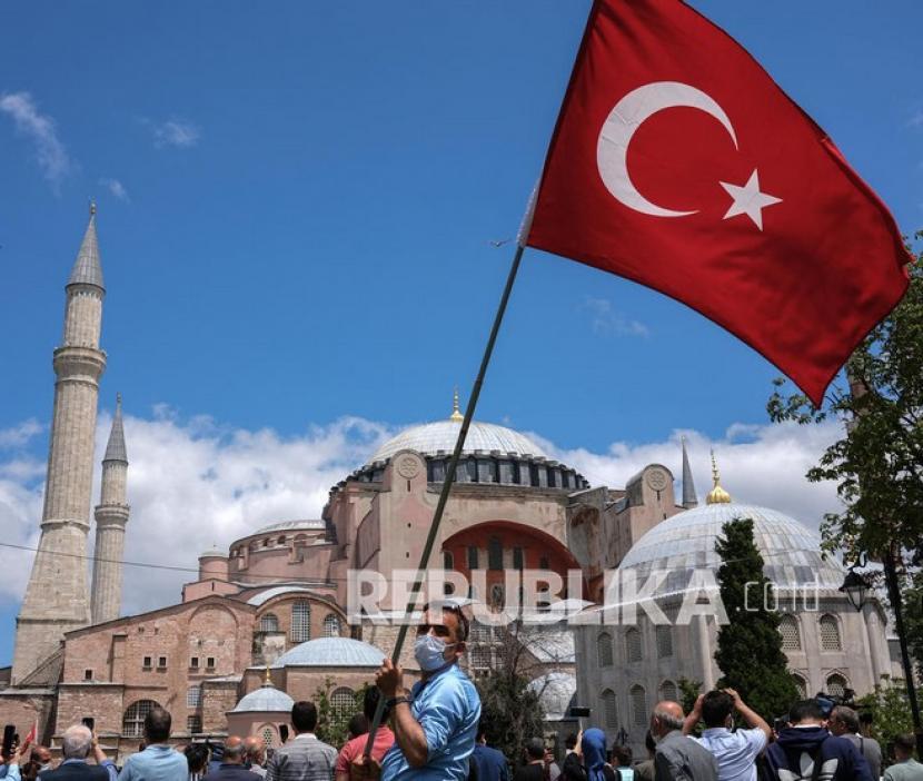 Seorang pria membawa bendera Turki di depan Masjid Hagia Sophia (ilustrasi). Dana Moneter Internasional (IMF) memperkirakan, pertumbuhan ekonomi Turki akan kuat tahun ini.