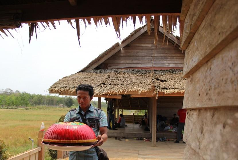 Seorang pria membawa nampan dalam tradisi Sepintu Sedulang