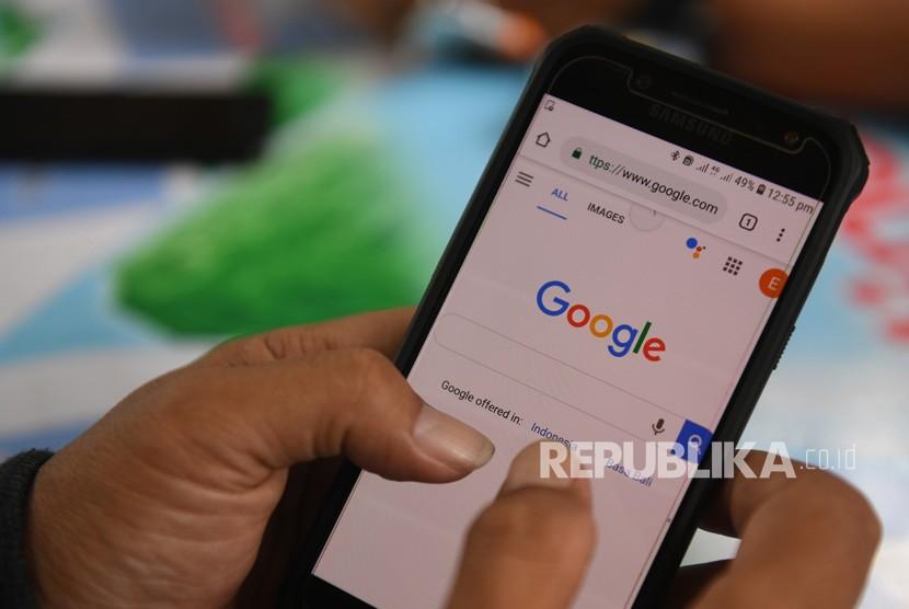 Seorang pria membuka laman Google dari gawainya di Jakarta, Jumat (12/4/2019).