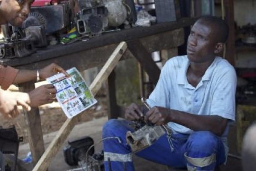 Seorang pria mendapatkan penjelasan sekaligus selebaran tentang ebola dari sebuah LSM di Conakry, Guinea.