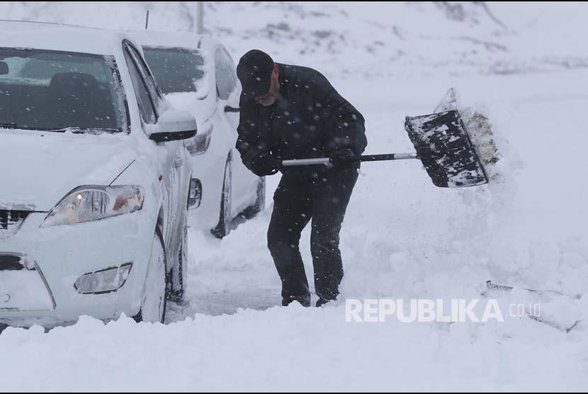 Seorang pria menyingkirkan salju yang menghalagi mobilnya (ilustrasi)