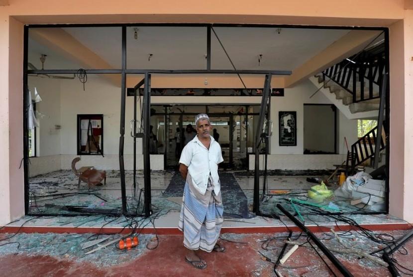 Seorang pria Muslim berdiri di depan Abbraar Masjid yang hancur akibat serangan massa di Kiniyama, Sri Lanks, Senin (13/5).