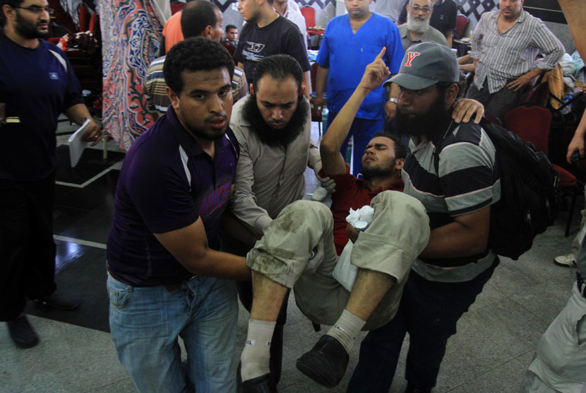 Seorang pria pendukung Presiden Mursi terluka dan dibawa ke rumah sakit darurat setelah ditembaki tentara di Kairo, Mesir, Senin (8/7). (AP/Ahmed Gomaa)