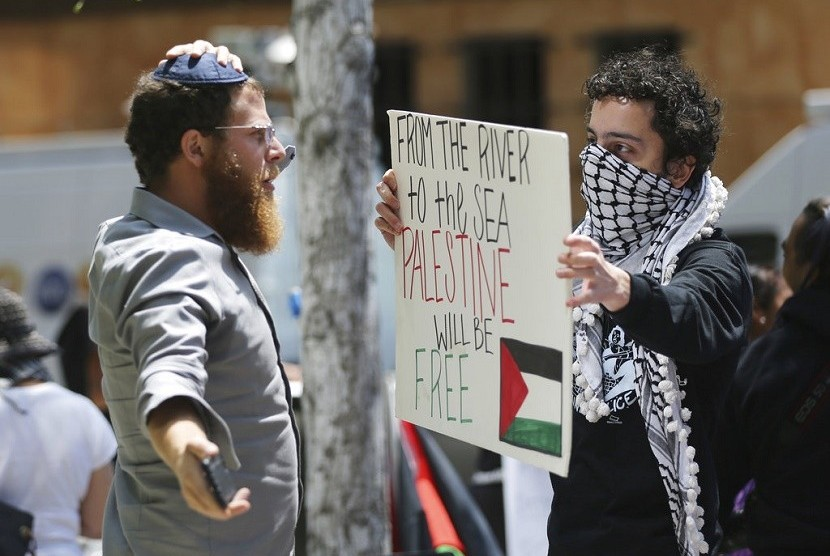 Seorang pria yahudi yang mengenakan yarmulke (kiri) menghadapi salah satu peserta demonstran yang memprotes kebijakan Pmeerintah AS yang memindahkan kedutaannya dari Tel Aviv ke Yerusalem, di luar konsulat Israel di Los Angeles, Senin (14/5). Tentara Israel menembak dan menewaskan sedikitnya 58 warga Palestina selama protes massal di sepanjang perbatasan Gaza pada hari Senin (14/5).