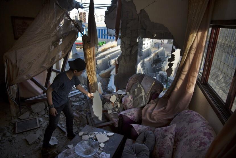 Seorang remaja Palestina di rumahnya yang hancur akibat serangan udara Israel di Gaza City, Palestina, Senin (6/5).
