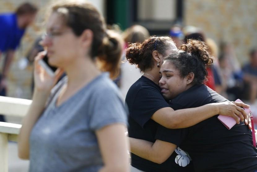 Seorang remaja putri berpelukan dengan ibunya seusai insiden penembakan di SMA Santa Fe, Texas, Amerika Serikat, Jumat (18/5).