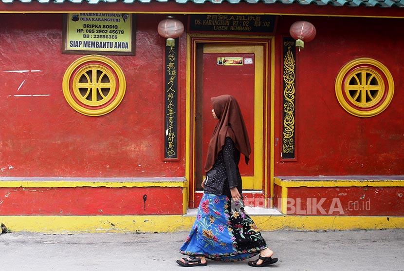 Seorang santri melintas di depan poskamling sebuah Pondok Pesantren di Kampung Wisata Pecinan, Lasem, Jawa Tengah. Bangunan kuno serta riwayat sejarah yang membentuk akulturasi budaya Jawa dan Tionghoa di kawasan tersebut.