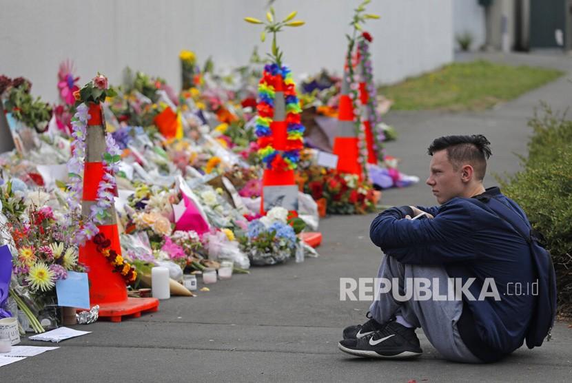 Seorang siswa memberikan penghormatan di sebuah taman di luar masjid Al Noor di Christchurch, Selandia Baru, Senin (18/3/2019).