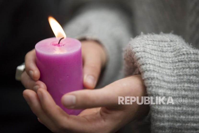 Seorang siswa memegang lilin saat peringatan untuk mengenang korban penembakan di luar Masjid Al Noor di Christchurch, Selandia Baru, Senin (18/3/2019).