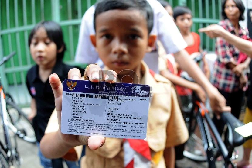 Seorang siswa menunjukan Kartu Indonesia Pintar (KIP) saat pembagian tiga jenis kartu sakti itu oleh Prsiden Joko Widodo kepada warga di wilayah Kampung Melayu, Jakarta Timur, Rabu (13/5).