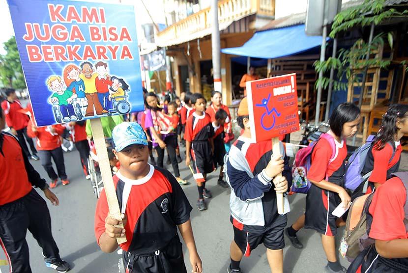 Seorang siswa penyandang disabilitas membawa poster berisikan kampanye tentang disabilitas saat mengikuti jalan santai memperingati hari Disabilitas Internasional di Blitar, Jawa Timur, Sabtu (3/12).