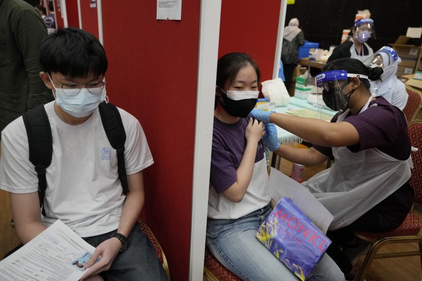 Seorang siswa sekolah menengah, tengah, menerima dosis vaksin Pfizer terhadap penyakit virus corona (COVID-19) di pusat vaksin di Shah Alam, Malaysia, Senin, 20 September 2021.
