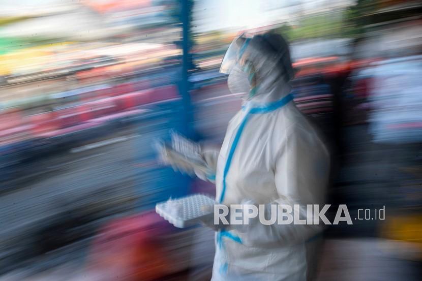 Seorang tenaga kesehatan yang mengenakan alat pelindung diri lengkap membawa sample tes usap (swab test) COVID-19 milik warga di kawasan Pasar Keputran, Surabaya, Jawa Timur (ilustrasi)