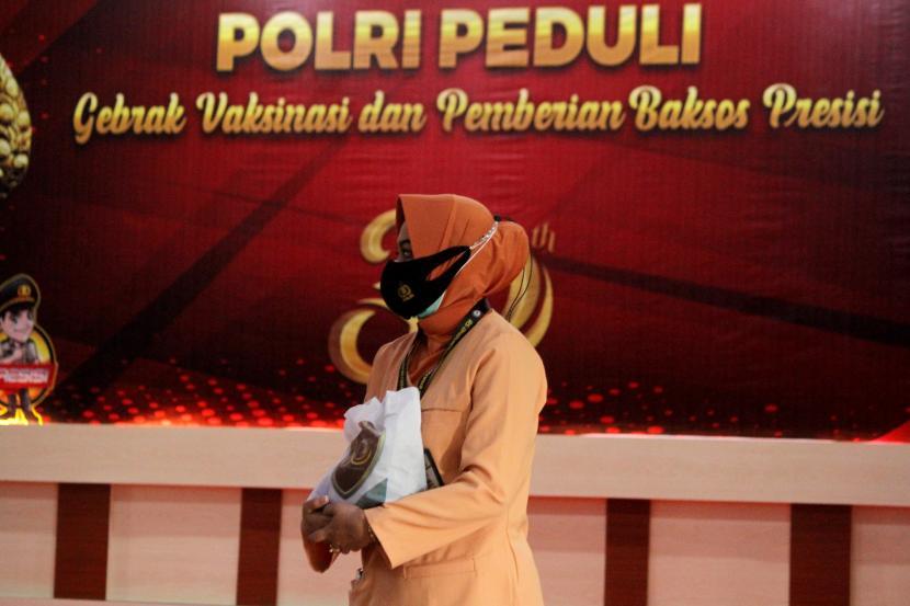 Seorang tenaga medis membawa paket bantuan sosial (bansos) yang dibagikan secara simbolis di Rumah Sakit Bhayangkara, Makassar, Sulawesi Selatan, Jumat (30/7/2021). Polda Sulawesi Selatan melaksanakan bakti sosial presisi dengan membagikan sebanyak 1.000 paket bantuan sosial bagi tenaga medis dan warga Papua yang berdomisili di daerah itu sebagai rangkaian kegiatan Polri Peduli COVID-19.