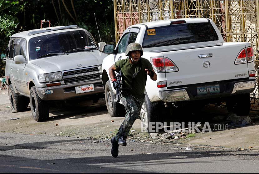 Seorang tentara  berlari saat mengepung pasukan bersenjata Maute di Marawi City, Filipina Selatan.
