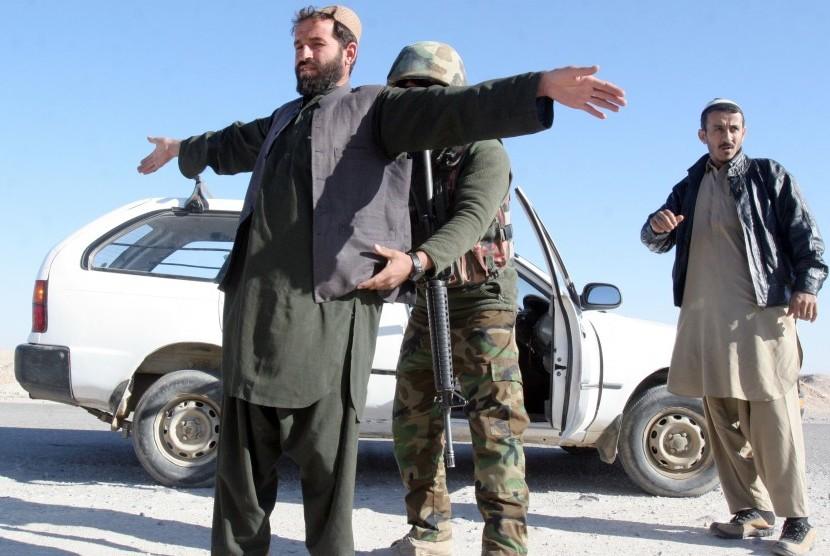 Seorang Tentara Nasional Afghanistan memeriksa seorang warga di sebuah pos pemeriksaan di provinsi Helmand, Afghanistan, Rabu 23/12.