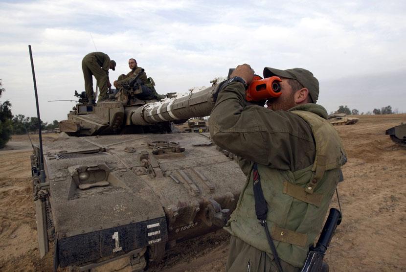Seorang tentara Zionis Israel memeriksa laras tank di dekat perbatasan dengan Jalur Gaza, Sabtu (17/11). (Reuters/Ronen Zvulun)