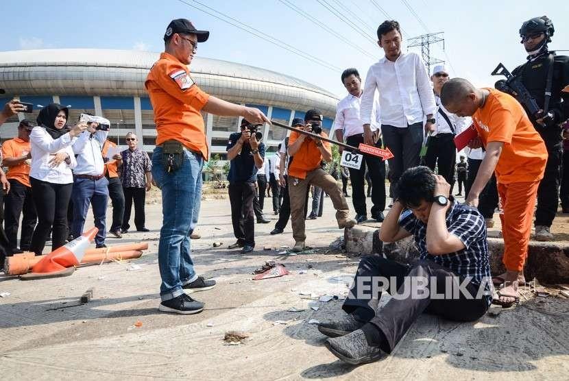 Seorang tersangka memperagakan tindakannya saat rekonstruksi pengeroyokan yang dilakukan oleh oknum bobotoh terhadap seorang suporter Persija, Haringga Sirla, di Stadion Gelora Bandung Lautan Api (GBLA), Bandung, Jawa Barat, Rabu (26/9).