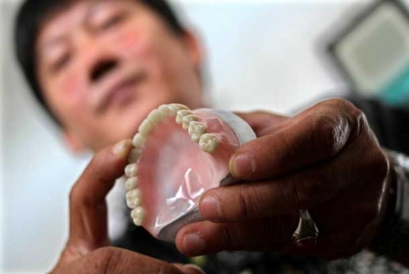 Seorang tukang gigi menunjukkan gigi palsu.