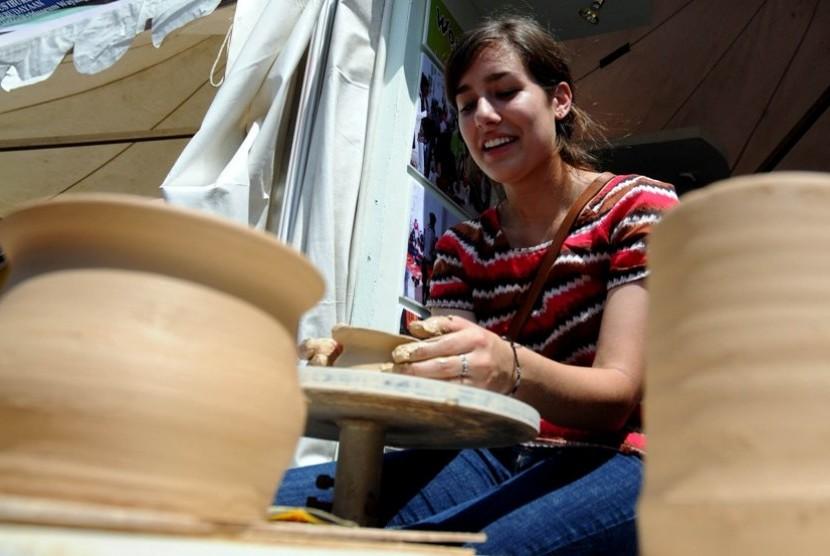 Seorang turis asing mencoba membuat keramik dengan tanah liat di salah satu stan acara Jakarta Festival Museum Day 2012, di Taman Fatahillah, Jakarta Barat, Sabtu (19/5). (Prayogi/Republika)