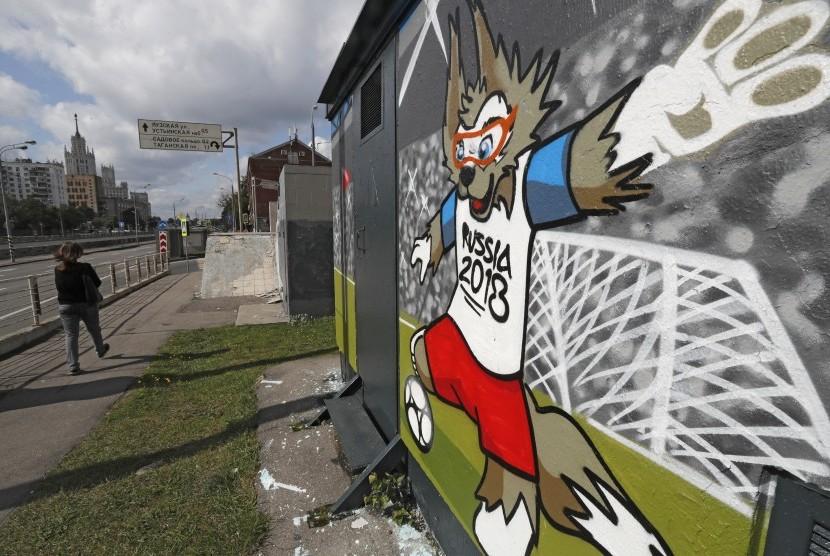 Seorang wanita berjalan di depan bangunan dengan grafiti Zabivaka, maskot Piala Dunia 2018, di pusat kota Moskow, Rusia. (ilustrasi)