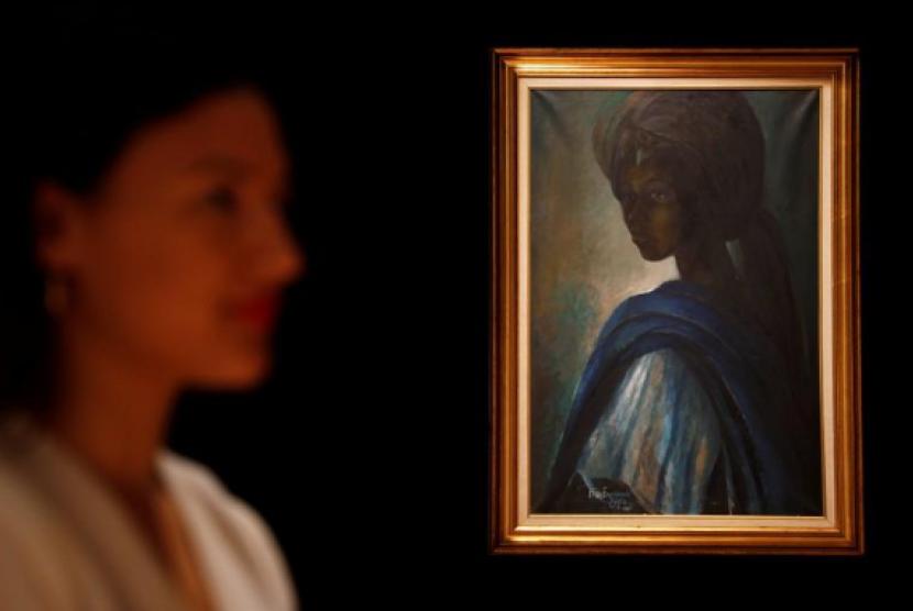 Seorang wanita dengan latar lukisan Tutu karya Ben Enwowu.