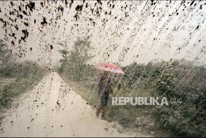 Seorang wanita menggunakan payung saat hujan (ilustrasi)