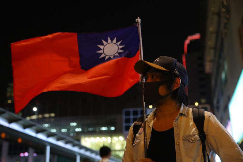 Seorang wanita memegang bendera Taiwan. Ilustrasi