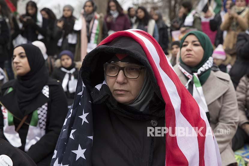 Seorang wanita mengenakan bendera Amerika di atas kerudungnya pada aksi menentang kebijakan Trump atas Yerusalem di President Park tidak jauh dari istana kepresidenan Gedung Putih Washington, DC, Jumat (8/12) waktu setempat, atau (9/12) dini hari WIB.