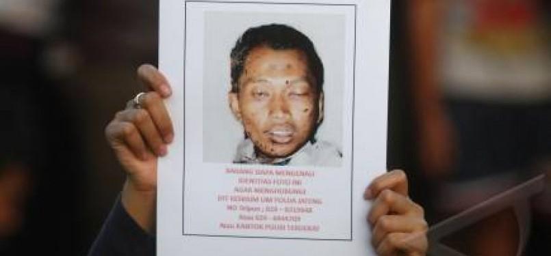 Seorang wanita nenunjukkan foto diduga tersangka pelaku bom bunuh diri di Gereja GBIS Kepunton, Solo, Minggu (25/9).
