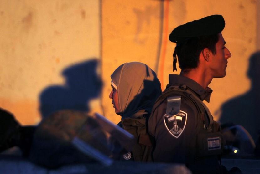 Seorang wanita Palestina berdiri di belakang polisi Israel saat melintasi pos pemeriksaan Qalandiya di Tepi Barat Ramallah, Jumat (10/8).  (Mohamad Torokman/Reuters)