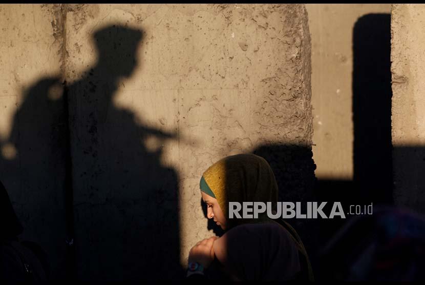 Seorang wanita Palestina melintasi pos pemeriksaan militer Israel di Qalandia menuju kawasan kompleks Al Quds di Jerusalem, Jumat (16/6). Israel melakukan pengawasan ketat termasuk menentukan siapa yang boleh memasuki komples masjid Al Aqsa tersebut.