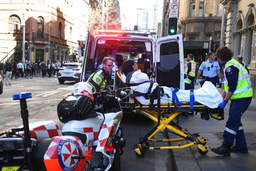 Seorang wanita yang menjadi korban penikaman dibawa dengan ambulans dari Hotel CBD di sudut King and York Street di Sydney, Australia, Selasa (13/8).