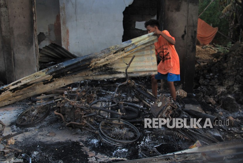 Seorang warga berada di bangkai dua unit sepeda motornya yang terbakar didalam rumahnya pasca keributan antar pemuda di Desa Gunung Jaya, Buton, Sulawesi Tenggara, Kamis (6/6/2019).